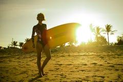 Silhouet met de gloed van de zonlens van het jonge gelukkige en aantrekkelijke surfermeisje het dragen brandingsraad stellen bij  royalty-vrije stock foto