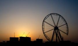 Silhouet op industriezone met kraan en reusachtig wiel onder mede Royalty-vrije Stock Foto's