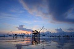 Silhouet traditionele visserijmethode die een bamboe vierkante onderdompeling gebruiken Stock Foto's