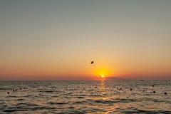 Silhouet van aangedreven glijscherm stijgende vlucht over het overzees tegen prachtige oranje zonsonderganghemel Recreatief delta stock foto
