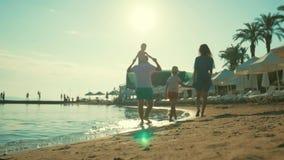 Silhouet van actieve familie die pret hebben en van samenhorigheid op het strand genieten bij zonsondergang stock footage