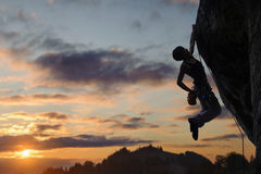 Silhouet van atletische vrouw die steile rotsmuur beklimmen stock foto's