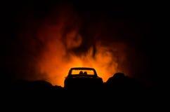 silhouet van auto met paar binnen op donkere achtergrond met lichten en rook Romantische scène Het concept van de liefde Royalty-vrije Stock Foto's