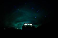 silhouet van auto met paar binnen op donkere achtergrond met lichten en rook Romantische scène Het concept van de liefde Stock Fotografie