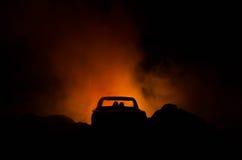silhouet van auto met paar binnen op donkere achtergrond met lichten en rook Romantische scène Het concept van de liefde Stock Foto