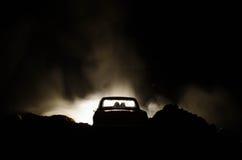 silhouet van auto met paar binnen op donkere achtergrond met lichten en rook Romantische scène Het concept van de liefde Royalty-vrije Stock Afbeeldingen