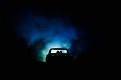 silhouet van auto met paar binnen op donkere achtergrond met lichten en rook Romantische scène Het concept van de liefde Royalty-vrije Stock Foto