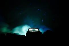 silhouet van auto met paar binnen op donkere achtergrond met lichten en rook Romantische scène Het concept van de liefde Stock Afbeeldingen