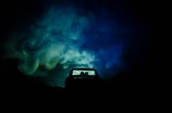 silhouet van auto met paar binnen op donkere achtergrond met lichten en rook Romantische scène Het concept van de liefde Royalty-vrije Stock Fotografie