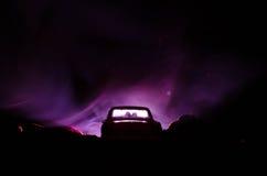 silhouet van auto met paar binnen op donkere achtergrond met lichten en rook Romantische scène Het concept van de liefde Royalty-vrije Stock Afbeelding