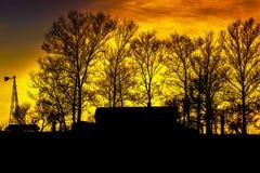 Silhouet van boerderij met windmolen en bomen Royalty-vrije Stock Afbeeldingen