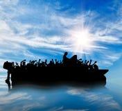 Silhouet van boten met vluchtelingen stock foto's