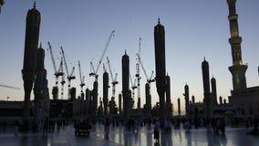 Silhouet van bouwkranen, Moslimpelgrims en ongeopende reuzeluifelparaplu tijdens zonsopgang in Al Madinah, Saudi-Arabië stock videobeelden