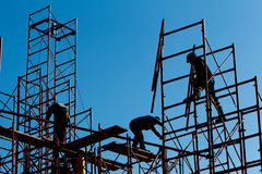 Silhouet van bouwvakkers tegen hemel op steigerwi Royalty-vrije Stock Afbeeldingen