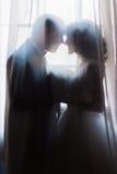 Silhouet van bruid en bruidegom die holdingsboeket omhelzen tegen het venster met gordijnen royalty-vrije stock foto