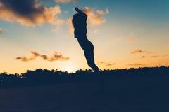 Silhouet van brunette die op strand bij zonsondergang, onbezorgde en spannings vrije vrouw op eiland springen Royalty-vrije Stock Fotografie