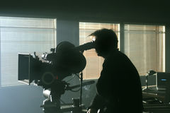 Silhouet van cameraman met de camera in de duisternis Stock Fotografie