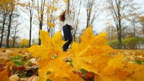 Silhouet van dansende vrouw in de herfstpark, gele esdoornbladeren in voorgrond stock video