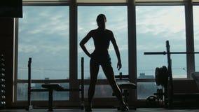 Silhouet van de aantrekkelijke vrouw die op een geschiktheidsstudio naar een venster gaan stock footage
