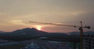Silhouet van de bouw in aanbouw met kraan tijdens zonsondergang, uitstekende filter stock videobeelden