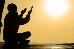 Silhouet van de christelijke jonge mens die met een kruis bij zonsopgang, Christian Religion-conceptenachtergrond bidden royalty-vrije stock afbeeldingen
