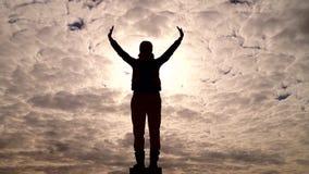 Silhouet van de een meisjes status van en verhogingen zijn handen aan de hemel zoals een vogel stock video