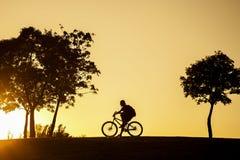 Silhouet van de fietserzitting op zijn fiets bij zonsondergang Stock Fotografie