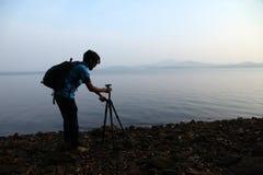 Silhouet van de fotograaf met driepoot Jonge mens die foto met zijn camera in de ochtend nemen dichtbij meer in India royalty-vrije stock fotografie