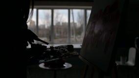 Silhouet van de hand van de kunstenaar met een borstel in haar handen, schildert zij op canvas stock videobeelden