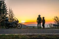Silhouet van de het meisjesmens van het fietserpaar en avonturenmotorfiets op de weg met zonsonderganglicht Bovenkant van bergen, royalty-vrije stock afbeelding