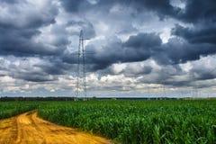 Silhouet van de hoogspannings elektrische pylon torens op de achtergrond van mooie onweerswolken dichtbij gele zandweg stock fotografie