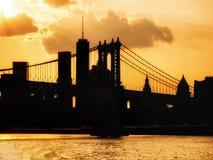 Silhouet van de horizon van de binnenstad van Manhattan en de Brug van Manhattan bij zonsondergang Stock Foto's