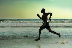 Silhouet van de jonge aantrekkelijke geschikte atletische en sterke zwarte Afrikaanse Amerikaanse mens die bij zonsondergangstran royalty-vrije stock afbeeldingen
