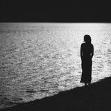 Silhouet van de jonge vrouw in kleding op het strand Royalty-vrije Stock Afbeelding