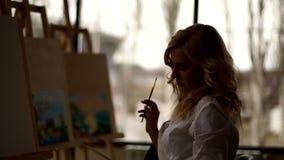 Silhouet van de kunstenaar met borstel in zijn hand dichtbij de schildersezel in tekeningsstudio stock videobeelden
