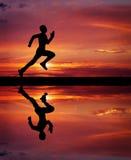 Silhouet van de lopende mens op zonsondergang vurige achtergrond. Stock Fotografie