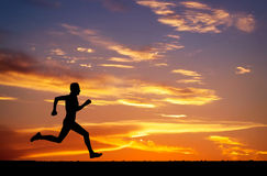 Silhouet van de lopende mens op zonsondergangachtergrond Royalty-vrije Stock Afbeelding