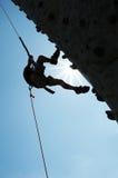 Silhouet van de mens bij het beklimmen van muur Royalty-vrije Stock Afbeelding