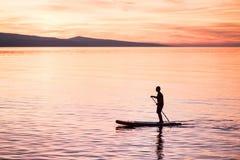 Silhouet van de mens bij zonsondergang die zich op peddelraad bevinden De vrije tijdsactiviteit van het de zomerstrand stock fotografie
