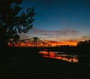 Silhouet van de mens bij zonsondergang op de achtergrond van de oude brug Stock Foto