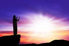 Silhouet van de mens die aan god met straal van licht bidden stock foto's