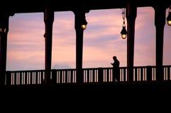 Silhouet van de mens die de brug kruisen Stock Afbeeldingen