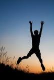 Silhouet van de mens die op gebied springen Stock Foto's
