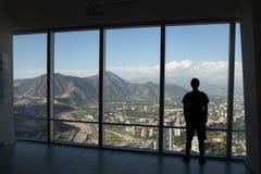 Silhouet van de mens die van mening van Gran Torre Santiago genieten stock foto