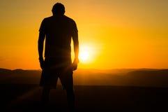 Silhouet van de mens die zonsondergang overdenken Stock Foto's