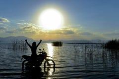 Silhouet van de mens en een motorfiets met zonsondergangachtergrond stock fotografie