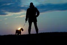 Silhouet van de mens en hond Stock Foto