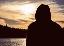 Silhouet van de mens met een kap in gouden zonsondergang die uit over een meer kijken royalty-vrije stock afbeelding