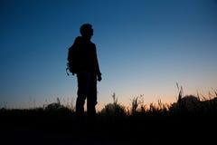 Silhouet van de mens met rugzak tegen donkere hemel Stock Fotografie