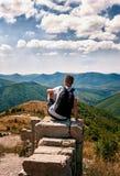 Silhouet van de mens met rugzakzitting met van hem terug naar de fotograaf op de grote rots en het bekijken het panorama van Stock Afbeelding